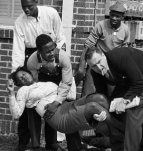 "FILE - In this March 7, 1965 file photo, S.W. Boynton is carried and another injured man tended to after they were injured when state police broke up a demonstration march in Selma, Ala. Boynton, wife of a real estate and insurance man, has been a leader in civil rights efforts. The day, which became known as ""Bloody Sunday,"" is widely credited for galvanizing the nation's leaders and ultimately yielded passage of the Voting Rights Act of 1965. (AP Photo/File)"